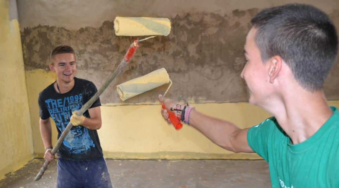 Construction volunteers in Ghana adding the finishing touches with paint.